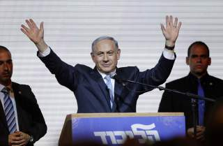 Israeli Prime Minister Benjamin Netanyahu waves to supporters at the party headquarters in Tel Aviv March 18, 2015. Netanyahu claimed victory in Israel's election after exit polls showed he had erased his center-left rivals' lead with a hard rightward shi