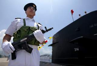 A Chinese Naval officer stands guard beside a submarine at the Ngong Shuen Chau Naval Base in Hong Kong April 30, 2004. China will expand the membership of the military's top decision-making body to