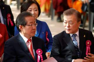 Moon Jae-in (R), presidential candidate of the Democratic Party of Korea, talks with Hong Joon-pyo, presidential candidate of the Liberty Korea Party, during a ceremony celebrating the birthday of Buddha at Jogye temple in Seoul, South Korea, May 3, 2017.