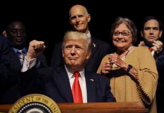 U.S. President Donald Trump thrusts his fist after signing an executive order reversing Obama administration Cuba policies as Florida Governor Rick Scott (C-rear), Cuban dissident and former prisoner Cary Roque and U.S. Senator Marco Rubio (R) look on at