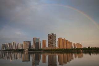 A rainbow appears over buildings reflected in water early morning in Shaoxing, China June 17, 2017. Picture taken June 17, 2017. REUTERS/Stringer