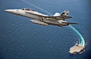 An F/A-18F Super Hornet jet flies over the USS Gerald R. Ford as the U.S. Navy aircraft carrier tests its EMALS magnetic launching system, which replaces the steam catapult, and new AAG arrested landing system in the Atlantic Ocean July 28, 2017. Picture