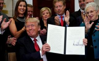 U.S. President Donald Trump smiles after signing an Executive Order to make it easier for Americans to buy bare-bone health insurance plans and circumvent Obamacare rules at the White House in Washington, U.S., October 12, 2017. REUTERS/Kevin Lamarque TPX