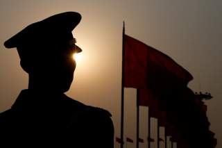 A paramilitary police officer is seen silhouetted in front of flags as he stands guard during the third plenary session of the Chinese People's Political Consultative Conference (CPPCC) in Beijing, China March 10, 2018.
