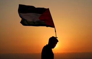 A demonstrator holds a Palestinian flag during a protest against Jewish settlements in the village of Ras Karkar, near Ramallah in the occupied West Bank August 30, 2018. REUTERS/Mohamad Torokma