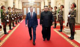 South Korean President Moon Jae-in is greeted by North Korean leader Kim Jong Un as he arrives at the headquarters of the Central Committee of the Workers' Party of Korea for their meeting in Pyongyang, North Korea, September 18, 2018. Pyeongyang Press Co