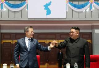 South Korean President Moon Jae-in and North Korean leader Kim Jong Un hold hands after watching the performance titled