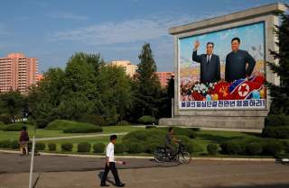 Residents pass by a painting of late North Korean leaders Kim Il Sung and Kim Jong Il in Pyongyang, North Korea, September 6, 2018. REUTERS/Danish Siddiqui
