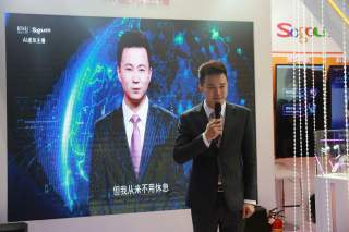 Xinhua news anchor Qiu Hao stands next to an AI virtual news anchor based on him, at a Sogou booth during an expo at the fifth World Internet Conference (WIC) in Wuzhen town of Jiaxing, Zhejiang province, China November 7, 2018. Picture taken November 7,