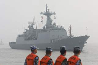 Chinese People's Liberation Army (PLA) Navy officials stand guard as a South Korean naval ship approaches the dock in Shanghai, China January 14, 2019. REUTERS/Stringer ATTENTION EDITORS - THIS IMAGE WAS PROVIDED BY A THIRD PARTY. CHINA OUT.