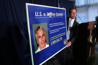 An employee of the Southern District of New York hangs a sign containing a photograph of Jeffrey Epstein, charged of sex trafficking of minors and conspiracy to commit sex trafficking of minors, in New York, U.S., July 8, 2019. REUTERS/Shannon Stapleton