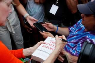 Democratic 2020 U.S. presidential candidate and U.S. Senator Elizabeth Warren (D-MA) autographs a copy of The Mueller Report with