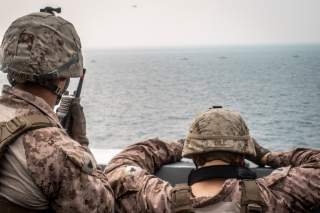 Marines onboard the amphibious transport dock ship USS John P. Murtha (LPD 26) watch nearby Iranian fast inland attack craft, as it transits the Strait of Hormuz, off Oman, in this undated handout picture released by U.S. Navy on August 12, 2019.