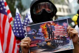 A protester holds up a sign featuring U.S. President Donald Trump in Central, Hong Kong, China September 8, 2019. REUTERS/Kai Pfaffenbach NO RESALES. NO ARCHIVES.