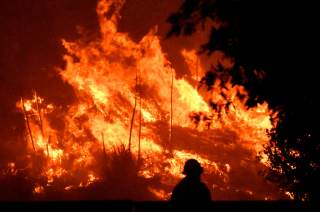 Firefighters battle a wind-driven wildfire called the Saddle Ridge fire in the early morning hours Friday in Porter Ranch, California, U.S., October 11, 2019. REUTERS/Gene Blevins