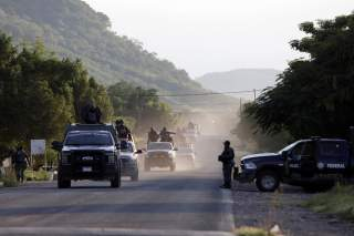 Security forces patrol along a road after police officers were killed during an ambush by suspected cartel hitmen in El Aguaje, in Michoacan state, Mexico October 14, 2019. REUTERS/Alan Ortega