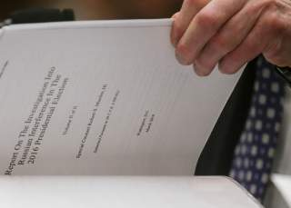 Former Special Counsel Robert Mueller references a copy of his report as he testifies before a House Judiciary Committee hearing on the Office of Special Counsel's investigation into Russian Interference in the 2016 Presidential Election on Capitol Hill