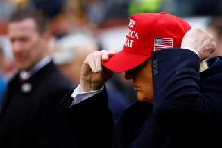 U.S. President Donald Trump puts on a Keep America Great hat during the annual Army-Navy collegiate football game at Lincoln Financial Field in Philadelphia, PA, U.S., December 14, 2019. REUTERS/Tom Brenner