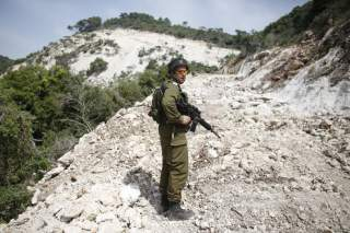 An Israeli soldier walks near the area where the Israeli army is excavating part of a cliff to create an additional barrier along its border with Lebanon, near the community of Shlomi in northern Israel April 6, 2016.
