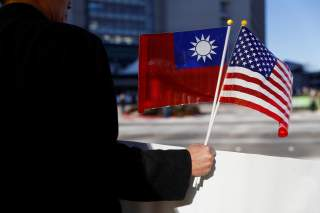 A demonstrator holds flags of Taiwan and the United States in support of Taiwanese President Tsai Ing-wen during an stop-over after her visit to Latin America in Burlingame, California, U.S., January 14, 2017. REUTERS/Stephen Lam