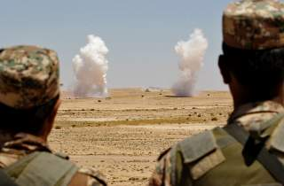 Jordanian soldiers watch smoke rising during an artillery drill, part of the