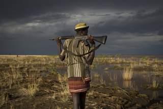 An armed Turkana man walks towards the shores of Lake Turkana near a temporary fishing camp some kilometres from Todonyang near the Kenya-Ethiopia border in northwestern Kenya October 12, 2013. The Turkana are traditionally nomadic pastoralists, but they