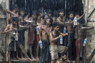 Migrants, who were found at sea on a boat, collect rainwater during a heavy rain fall at a temporary refuge camp near Kanyin Chaung jetty, outside Maungdaw township, northern Rakhine state, Myanmar June 4, 2015. Myanmar on Wednesday landed the boat with 7