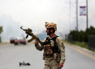 A member of Afghan security forces holds a rifle at the site of an attack near the Afghan parliament in Kabul, Afghanistan June 22, 2015. A Taliban suicide bomber and six gunmen attacked the Afghan parliament on Monday, wounding at least nineteenpeople a