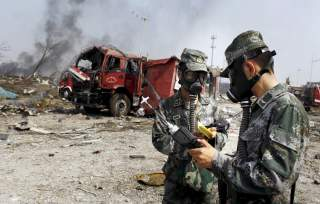 Soldiers of the People's Liberation Army anti-chemical warfare corps work next to a damaged firefighting vehicle at the site of Wednesday night's explosions at Binhai new district in Tianjin, China, August 16, 2015.
