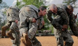 Then U.S. Army First Lieutenant Kirsten Griest (C) and fellow soldiers participate in combatives training during the Ranger Course on Fort Benning, Georgia, in this handout photograph taken on April 20, 2015 and obtained on August 20, 2015. When Griest an