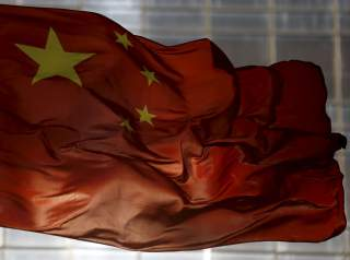 China's national flag flutters at a business district in Beijing, October 29, 2015. China's Premier Li Keqiang said China requires annual growth of at least 6.53 percent over the next five years, Bloomberg reported, citing unidentified sources. Chinese le