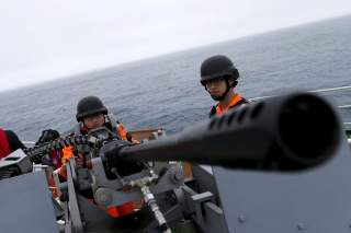 Taiwanese Coast Guard Administration guard demonstrate a machine gun on the docks of the 3000-ton