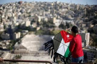 A boy flies his kite decorated with the Jordanian national flag during an event celebrating spring at the Citadel in Amman, Jordan, April 15, 2016. REUTERS/Muhammad Hamed