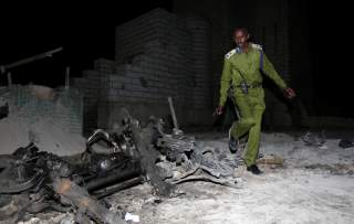 A Somali policeman inspects the scene of a suicide car explosion near the parliament in the capital Mogadishu, November 5, 2016. REUTERS/Feisal Oma