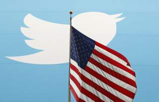 The Twitter Inc. logo is shown with the U.S. flag during the company's IPO on the floor of the New York Stock Exchange in New York, November 7, 2013. REUTERS/Lucas Jackson/File Photo