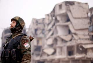 A member of forces loyal to Syria's President Bashar al-Assad stands near damaged buildings in Aleppo's Salaheddine district, Syria December 16, 2016. REUTERS/Omar Sanadiki
