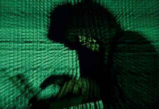 A man holds a laptop computer as cyber code is projected on him in this illustration picture taken on May 13, 2017. REUTERS/Kacper Pempel