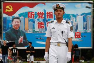 A People's Liberation Army Navy soldier stands in front of a backdrop featuring Chinese President Xi Jinping at a naval base in Hong Kong, China July 8, 2017. REUTERS/Bobby Yip