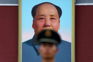 A paramilitary policeman stands guard under a giant portrait of late Chinese Chairman Mao Zedong at the Tiananmen gate in Beijing, China July 14, 2017. REUTERS/Damir Sagolj