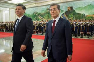 South Korean President Moon Jae-In and Chinese President Xi Jinping review the Chinese honour guard during a welcome ceremony at the Great Hall of the People in Beijing, China December 14, 2017. REUTERS/Nicolas Asfouri/Pool