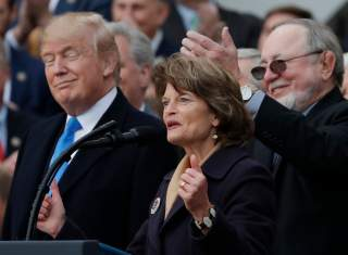 U.S. President Donald Trump stands with with Alaska's Sen. Lisa Murkowski (R-AK), and Rep Don Young (R-AK) as he celebrates with Congressional Republicans after the U.S. Congress passed sweeping tax overhaul legislation on the South Lawn