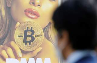 A man stands near an advertisement of a cryptocurrency exchange in Tokyo, Japan March 30, 2018. Picture taken March 30, 2018. REUTERS/Toru Hanai