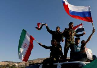 Syrians wave Iranian, Russian and Syrian flags during a protest against U.S.-led air strikes in Damascus,Syria April 14,2018.REUTERS/ Omar Sanadiki TPX IMAGES OF THE DAY