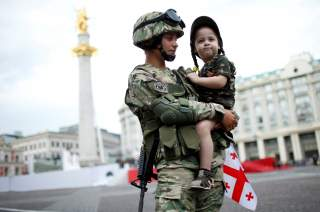Servicewoman, Tamar Kurkumuli, 25, holds her 3-year-old daughter Nino, before the oath-taking ceremony as Georgia marks the 100th anniversary of its independence in Tbilisi, Georgia, May 26, 2018. REUTERS/David Mdzinarishvili