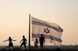 Israeli kids play next to an Israeli flag next to the Israeli Syrian border at the Israeli-occupied Golan Heights, Israel July 23, 2018. REUTERS/Ronen Zvulun