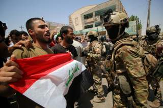 Iraqi security forces stand guard as demonstrators protest in front of Basra provincial council building, demanding jobs and better state services, in Basra, Iraq July 31, 2018. REUTERS/Essam al-Sudani