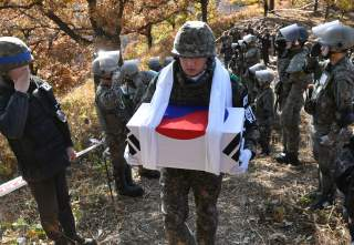 A South Korean soldier carries a casket containing a piece of bone believed to be the remains of an unidentified South Korean soldier killed in the Korean War in the Demilitarized Zone (DMZ) dividing the two Koreas in Cheorwon, South Korea October 25, 201