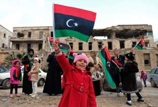 A child carries the flag of Libya during a celebration of the eighth anniversary of the revolution, in Benghazi, Libya February 17, 2019. REUTERS/Esam Omran Al-Fetori