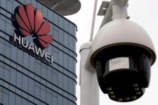 FILE PHOTO: A surveillance camera is seen in front of the Huawei logo outside its factory campus in Dongguan, Guangdong province, China, March 25, 2019. REUTERS/Tyrone Siu/File Photo