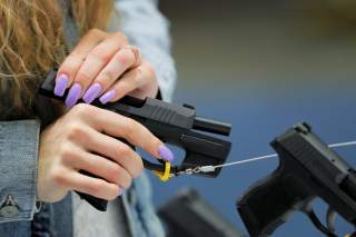 A woman handles a gun inside of the Sig Sauer booth during the National Rifle Association (NRA) annual meeting in Indianapolis, Indiana, U.S., April 28, 2019. REUTERS/Lucas Jackson